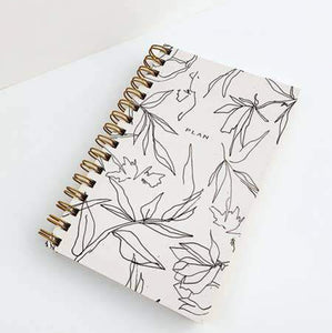 "Sprial bound day planner with abstract flowers on the cover and the word ""plan""."