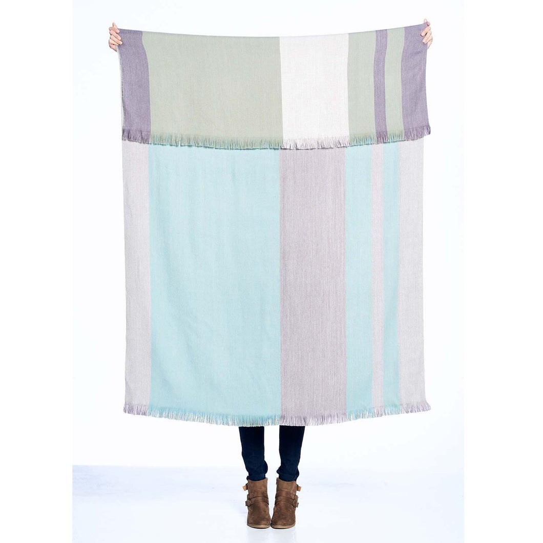 A person who cannot be seen holds up a large throw with a folded over top.  The photo is showing that the throw has colored block pattern on each side in pastel pinks, blues, and purples.