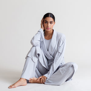 A woman sits on the floor wearing loose fitting light blue loungewear.