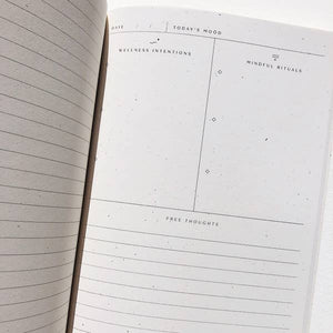 "An interior photo of the Wellness Ritual Journal.  The left side reads ""Wellness Intentions"" and left side reads Mindful Rituals.  The bottom of the page has blank lines and a header reading ""Free Thoughts""."