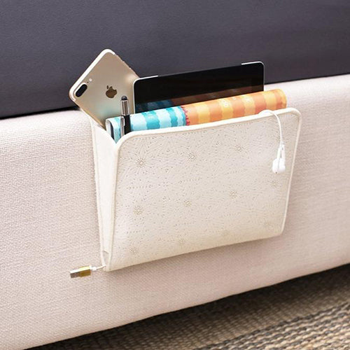 A lightcolored pocket to attach to the side of your bed holds a book, electronics, pen, and phone.