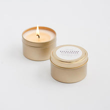 Load image into Gallery viewer, Photo of two candles in gold tins. One is open and burning and one is closed.