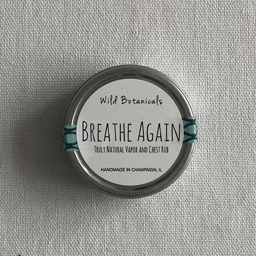 A display photo of Breath Again Natural Vapor and Chest Rub.  Product is packaged in a small tin with a sticker label on top.