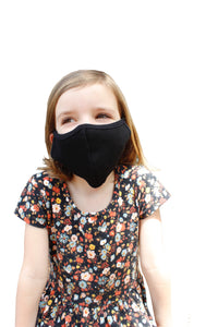 Little girl wears a solid black kids face mask.
