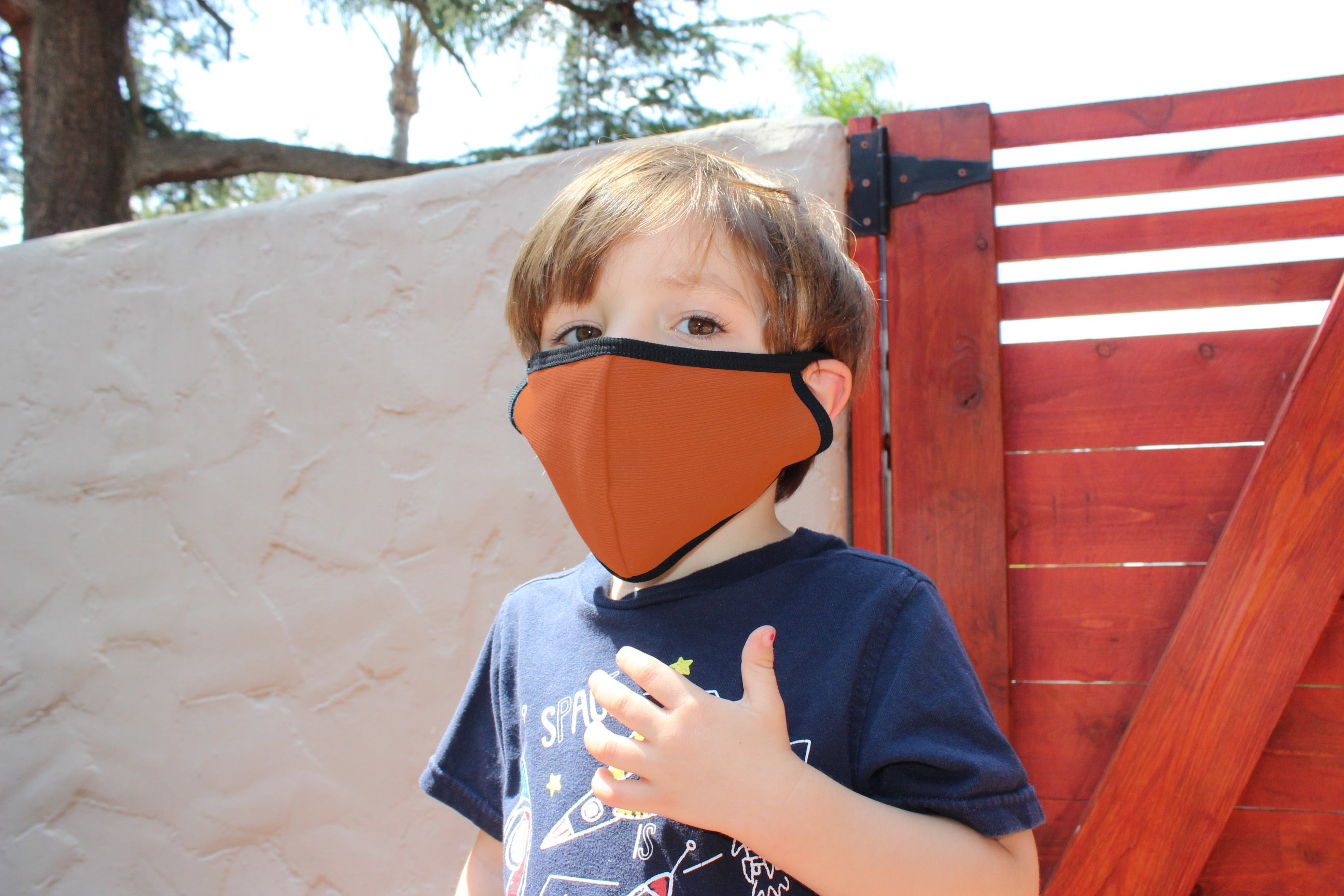 Little boy wears burnt orange kids face mask.