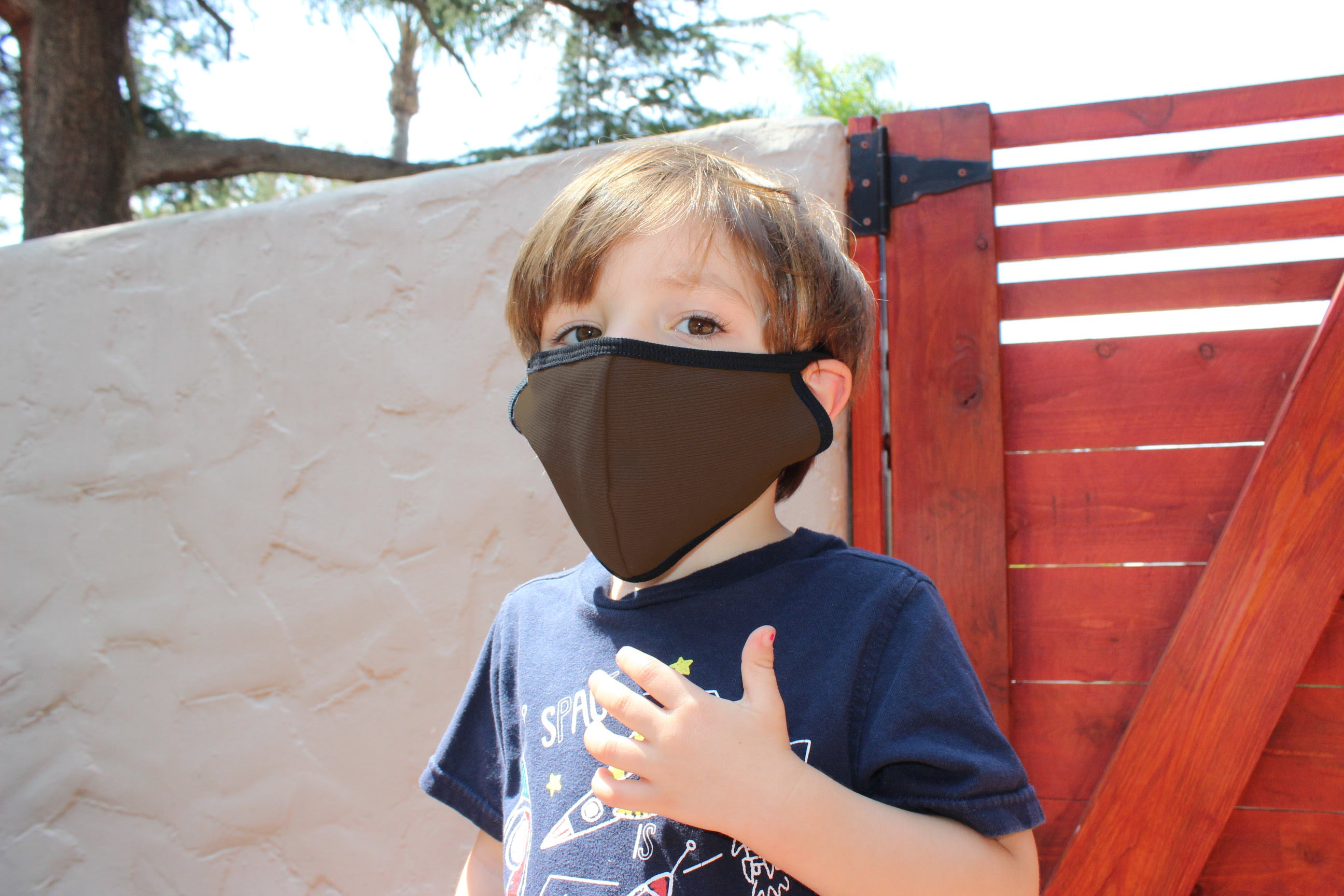 Little boy wears a brown kids face mask.