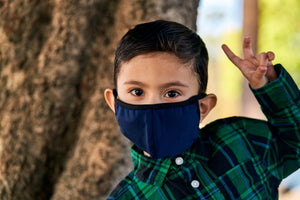 Little boy wears a dark blue kids face mask with black trim.