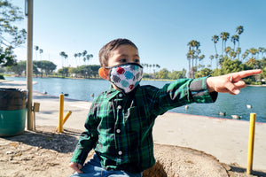 Little boy wears a face mask with a robot pattern on it.