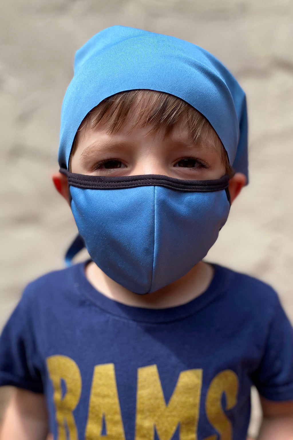 Little boy wearing a baby blue face mask and a matching head wrap