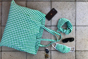Green gingham face mask with white trim lays out with a matching scarf and tote bag. Image styled with a phone, sunglasses, and a set of keys.