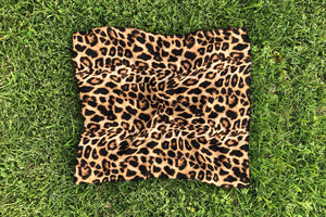 Leopard pattern square cut scarf lays flat on the grass.