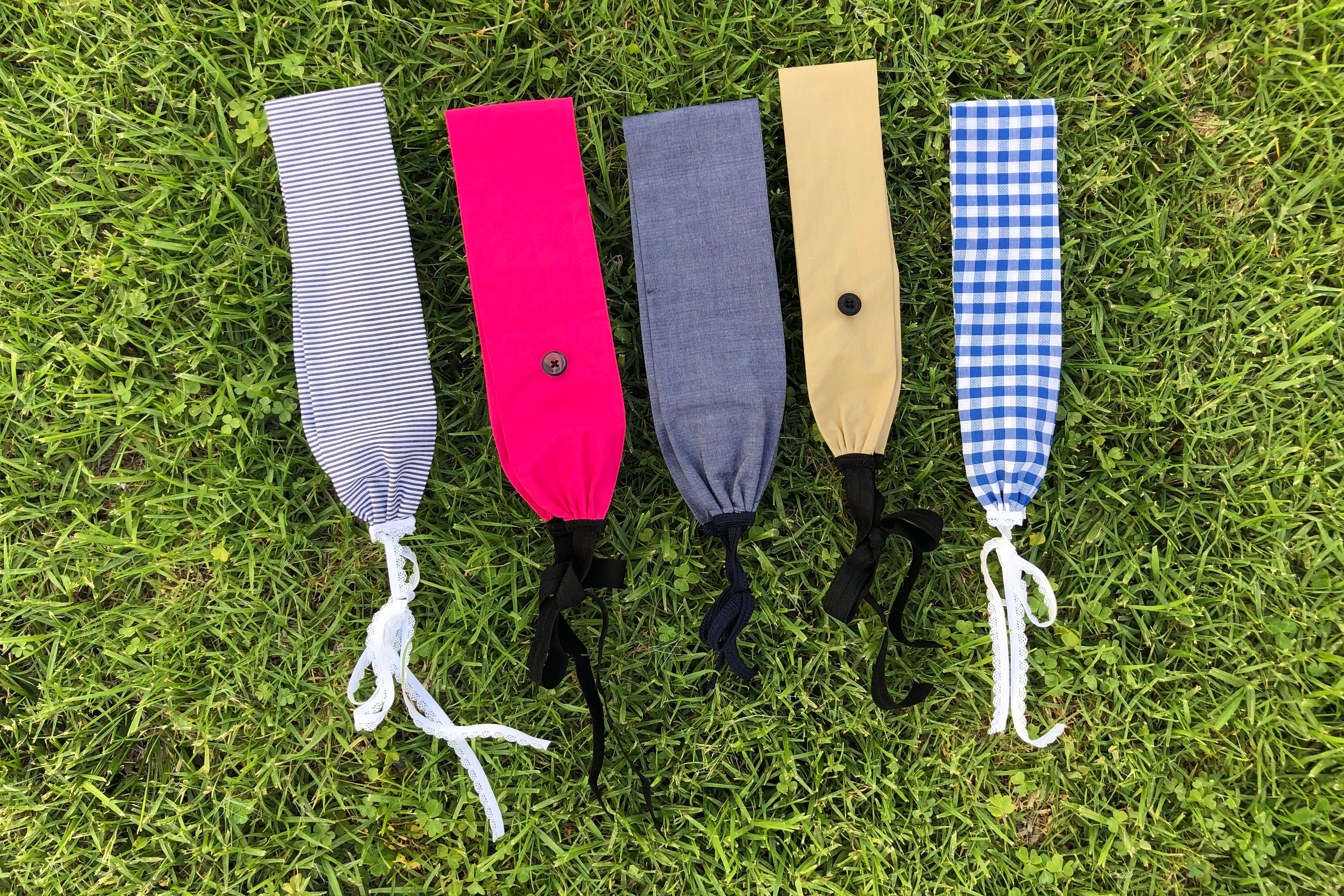 Five headbands lay flat in the grass.