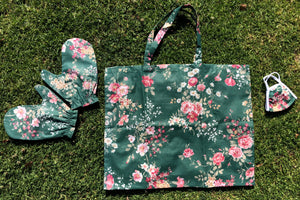 Green floral matching set of a face mask, mittens, and a tote bag lay flat on the grass.