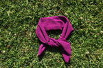 Load image into Gallery viewer, Fuchsia scarf tied into a head band lays on the grass.