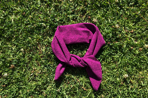 Fuchsia scarf tied into a head band lays on the grass.