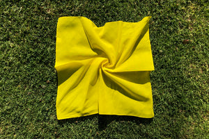 Yellow square cut bandana lays flat in the grass.