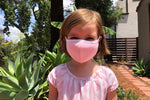 Load image into Gallery viewer, A little girl wears a light pink kids face mask with white trim.