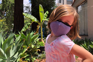 Little girl wears a purple kids face mask with black trim.