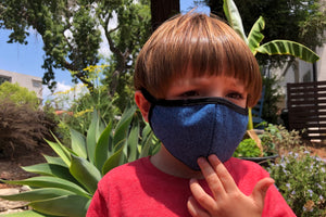 Little boy wears a blue heather kids face mask with black trim.