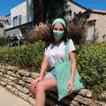 Load image into Gallery viewer, Woman wears a the green gingham set that includes a scarf, face mask, and tote bag.