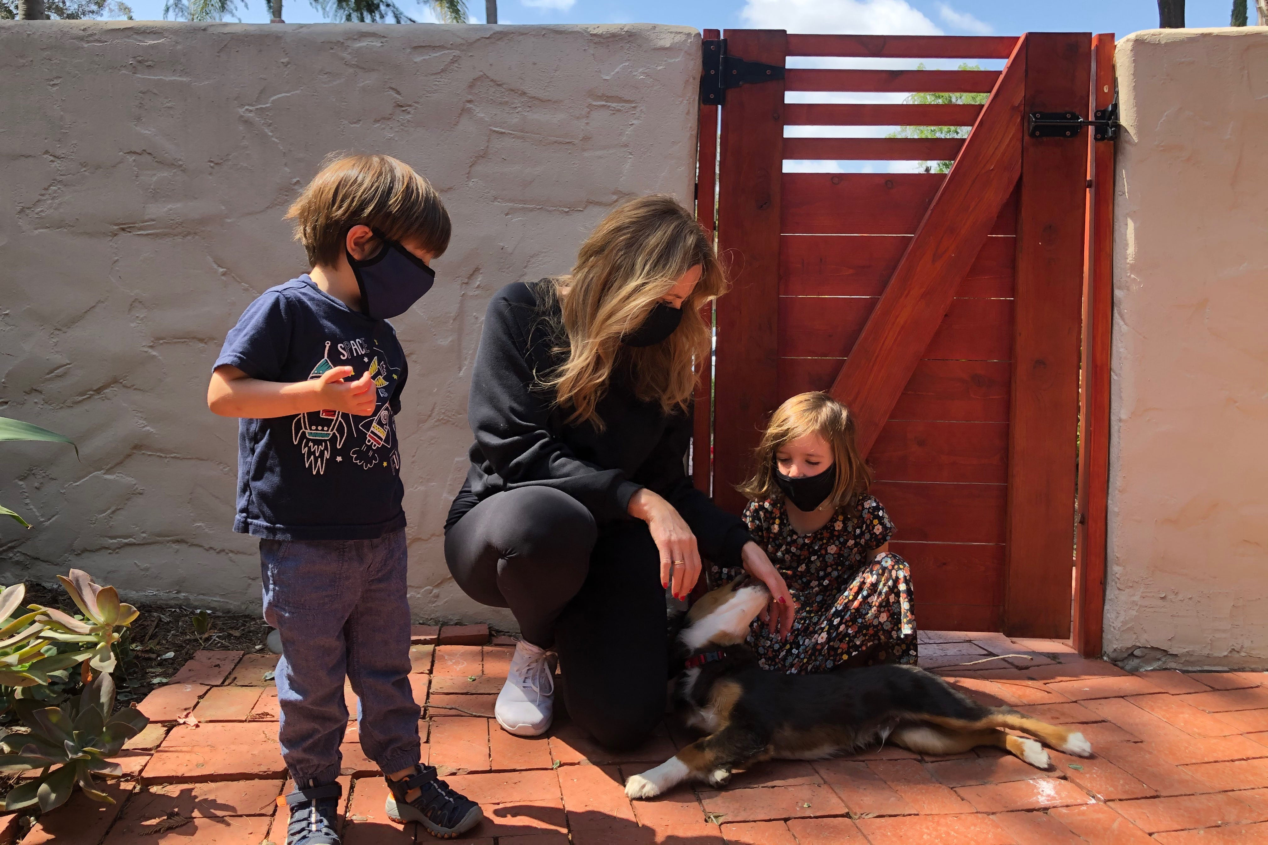 A woman, two kids, and a puppy play in a courtyard while wearing face masks.
