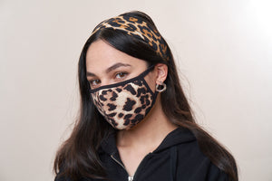 Woman wearing a leopard print face mask with a matching scarf that is tied as a headband.