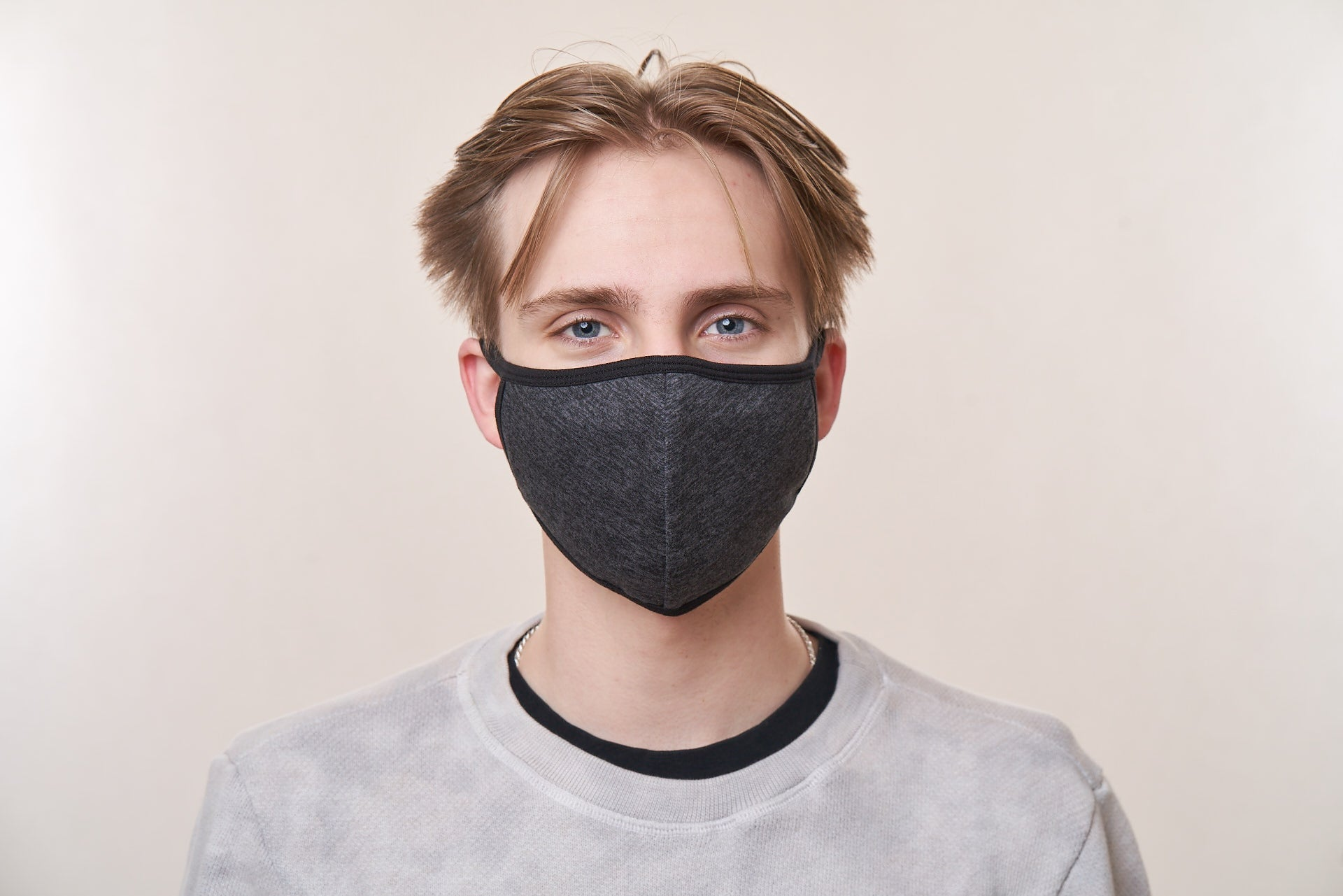 Young man wearing a charcoal heather face mask with black trim.