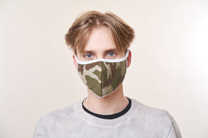 A young man wearing a green camo face mask with white trim.