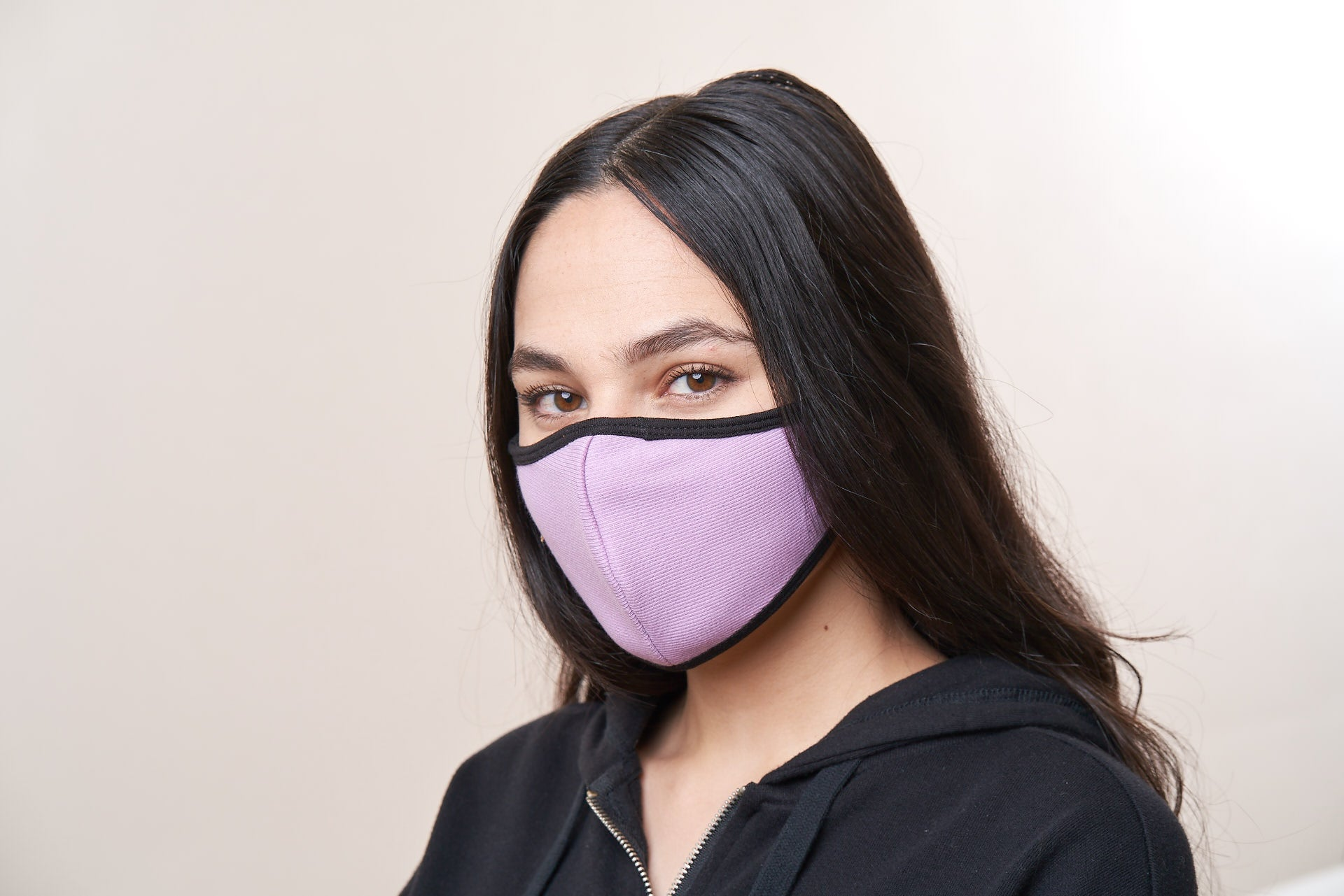 Woman wearing a lavender face mask with black trim.