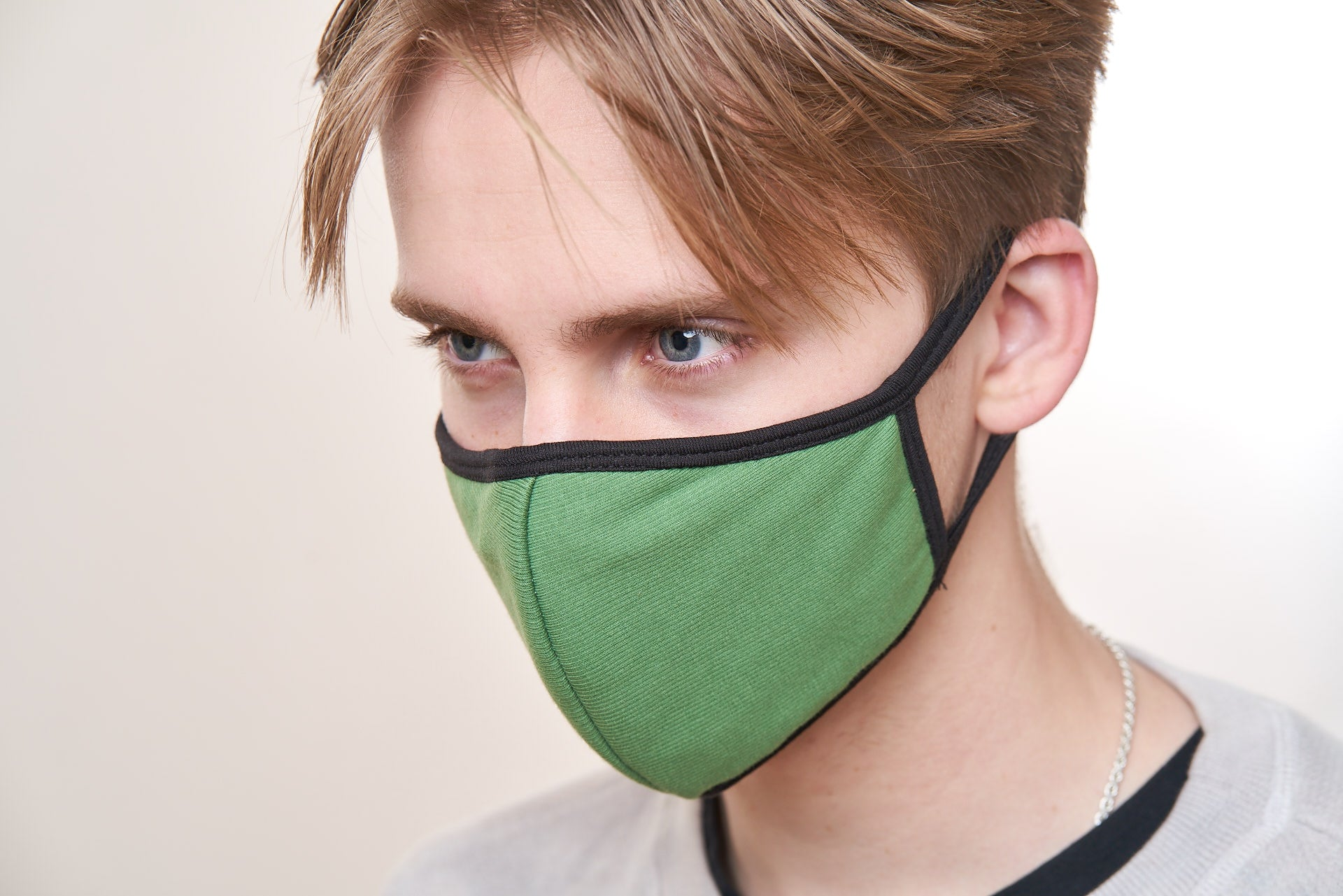 Young man wears a green face mask with black trim.