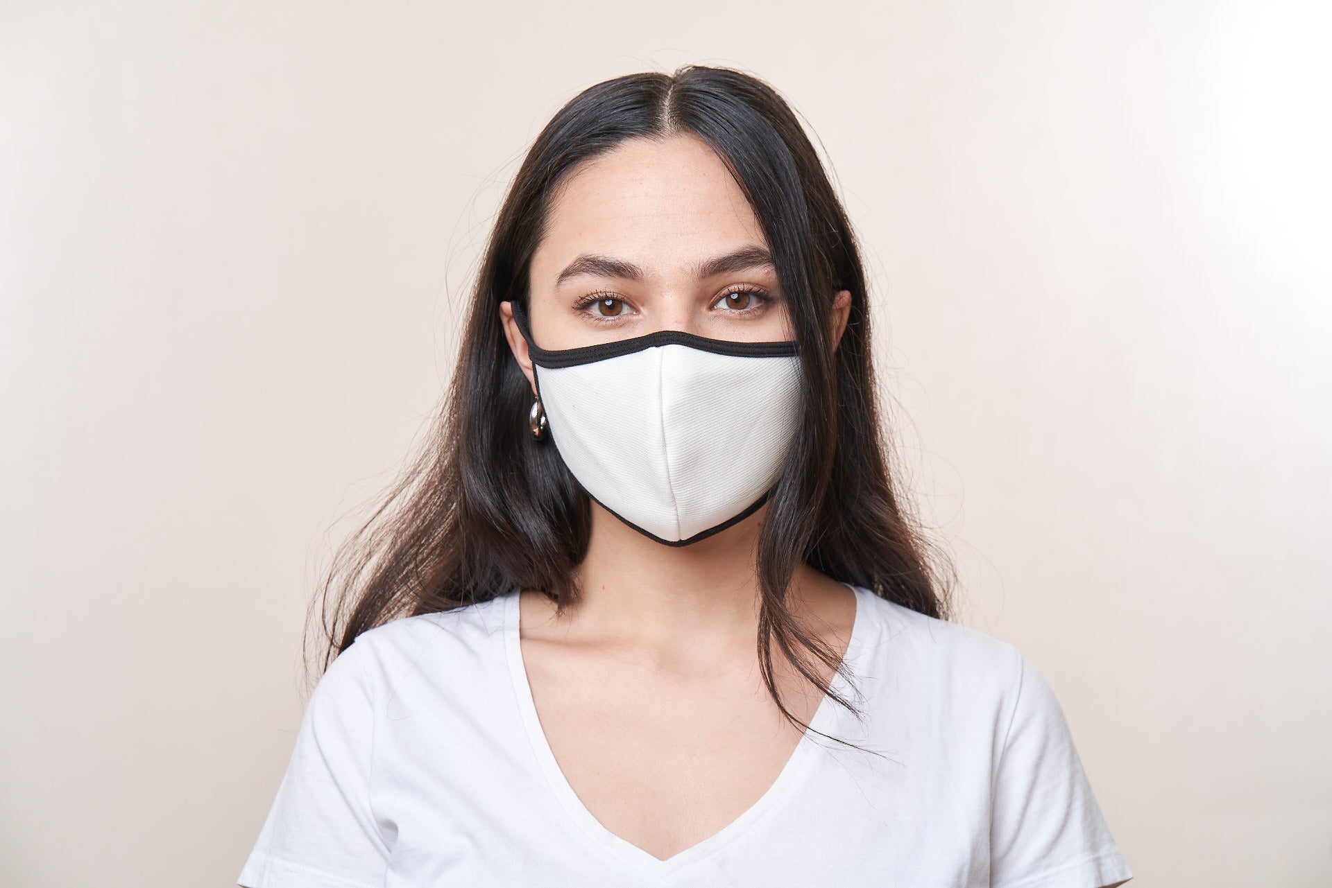 Woman wearing a white face mask with black trim.