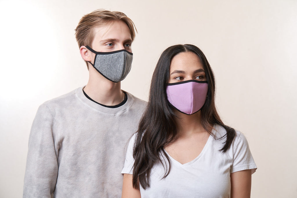 A man wearing a gray face mask with a woman wearing a lavender face mask.