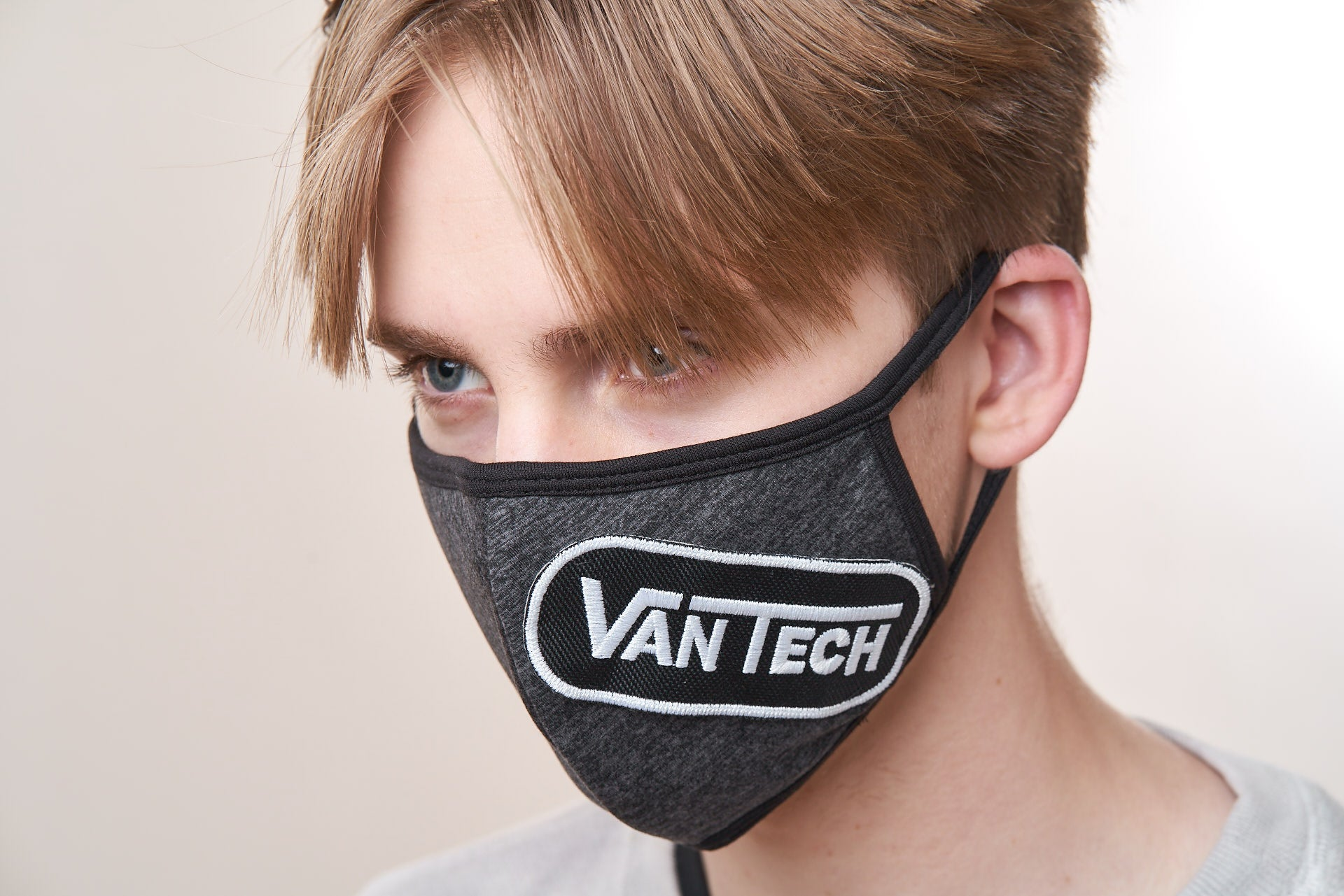 Young man wears a charcoal face mask with a VanTech logo patch on it.