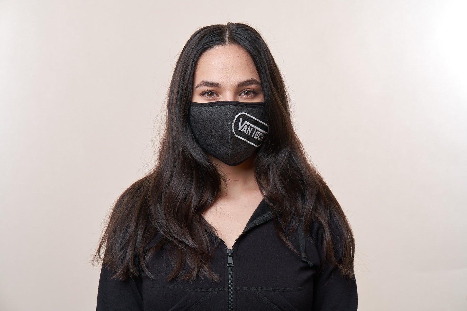 Woman wears a charcoal face mask with a VanTech logo patch on it.
