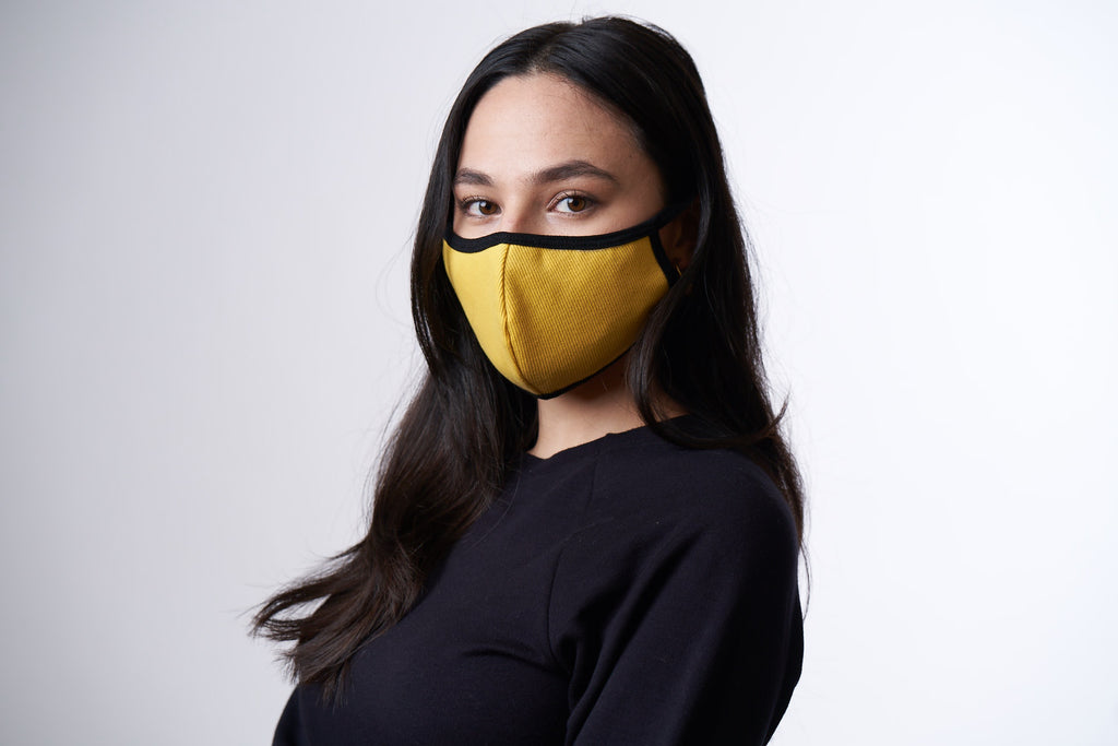 Woman wearing a yellow face mask with black trim.