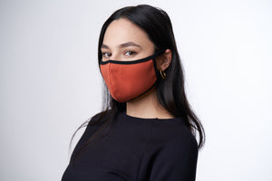 Woman wearing a burnt orange face mask with back trim.