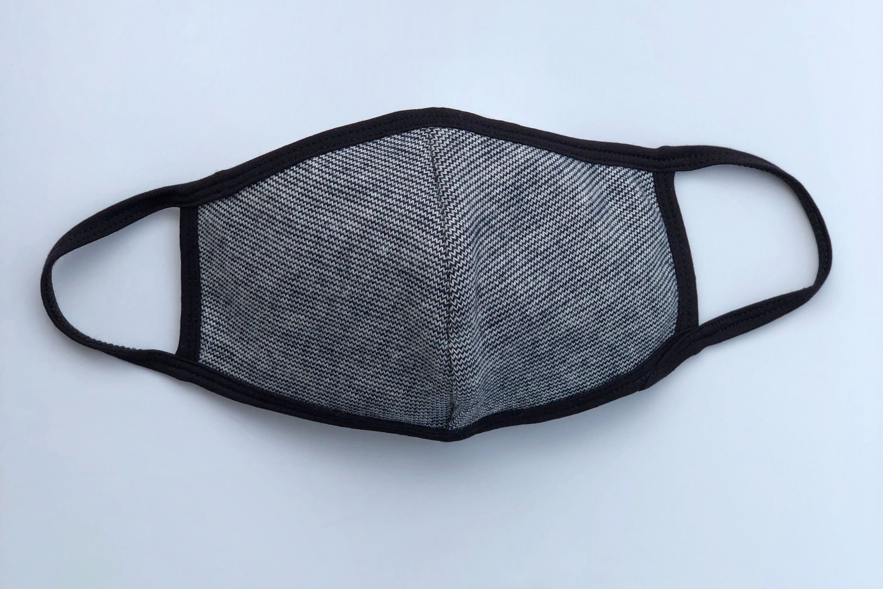 Face mask with a small blue and white zig zag pattern, with black trim.