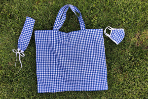 A matching set of a blue gingham face mask, headband, and tote bag lay flat in the grass.