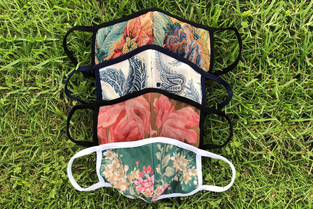 Four floral patterned face masks are laid out in the grass.
