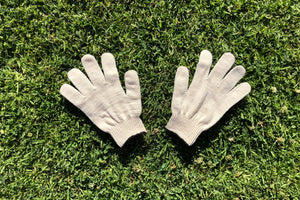 A pair of off white cotton spandex gloves laying out in the grass.