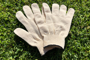 A close up of a pair of off white cotton spandex gloves laying out in the grass.