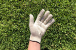 Load image into Gallery viewer, A hand wearing an off white cotton/spandex washable reusable glove.