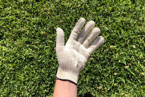A hand wearing an off white cotton/spandex washable reusable glove.