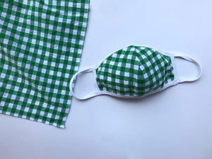 Green gingham face mask with white trim lays out next to a matching square cut scarf.