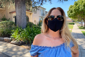 Woman models a black face mask with a pair of sunglasses.