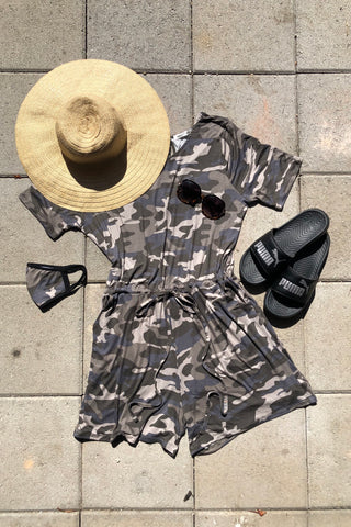 A green and blue camo romper flat lay, styled with a big sun hat, sunglasses, slides, and a matching face cover.
