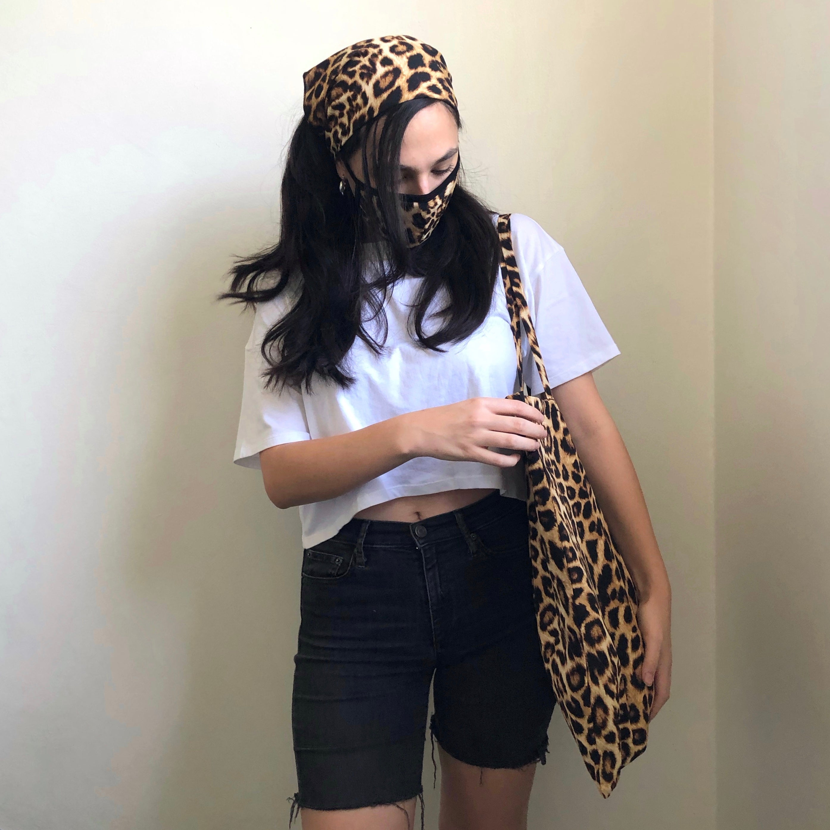 Woman models the leopard matching set that includes a scarf, face mask, and tote.