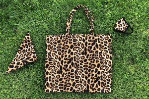 Leopard pattern tote, scarf, and face mask lay flat on the grass.
