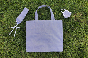 A matching set of a striped navy face mask, headband, and tote bag lay flat in the grass.