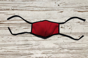 The Scout face mask in red that features two long ties so that the wearer can adjust to their desired fit.